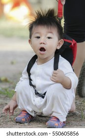 Cute smiling baby boy learning to walk and make his first steps