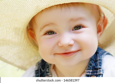 Cute smiling baby girl face close up outdoor in summer day