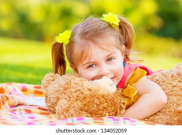 Cute smiling baby girl hugging soft bear toy, sweet kid having fun outdoors in day care, laying down on green grass in spring
