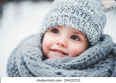 cute smiling baby girl winter close up portrait in warm knitted hat and scarf