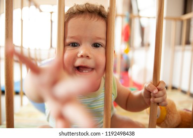 Cute smiling baby looking through the wooden bars of his crib or playpen with a happy smile indoors in the nursery