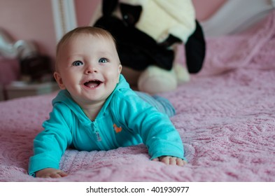 Cute smiling baby lying on tummy in parent's bed with a big toy dog on background. Happy baby.