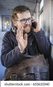 Cute, smiling bearded man in glasses sits in a departing train and waving his hand at the window