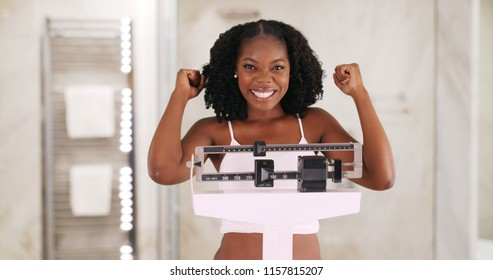 Cute smiling black female stands on weight scale cheering weight loss