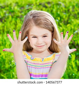 Cute smiling blond little girl with many-coloured manicure