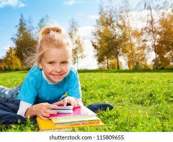 Cute smiling blonde girl in park laying on green grass in sunny weather