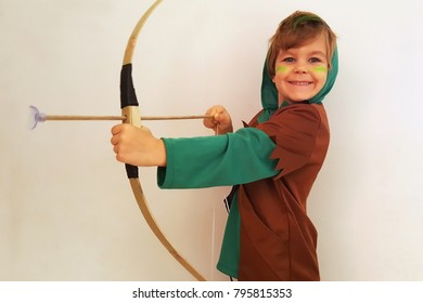 Cute smiling boy in an archer costume posing against the wall, bow and arrow in his hand, long hair. Ready for Purim party