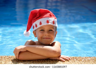 Cute smiling boy in blue water pool looking into camera, santa hat on his head. Sunny summer mood. Concept: christmas or Happy New Year holiday in hot country