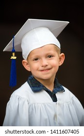 Cute smiling boy in cap and gown after kindergarten graduation