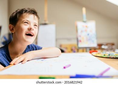 Lächelnder Junge mit Down-Syndrom spielen mit Farbe im Malerstudio für spezielle bedürftige Kinder.