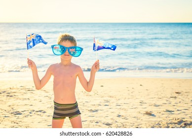 Cute smiling boy standing on the beach and holding Australian flags on Australia day