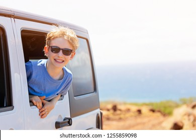 cute smiling boy in sunglasses looking out from car window enjoying family road trip adventure at the tropical island of lanai, hawaii, copy space on right, sun glare
