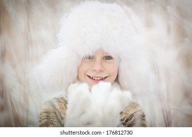 A cute smiling boy in a white fur cap with ear-flaps on a frosty winter day close up