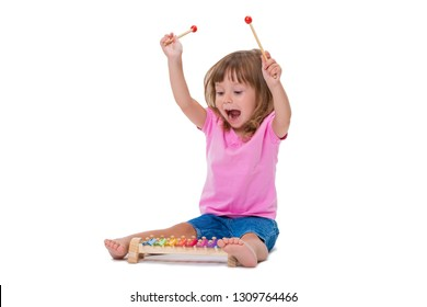 Cute smiling cheerful positive girl 3 years old playing with musical instrument toy xylophone isolated on white background