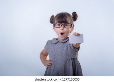 Cute smiling child with glasses holding discount white card in her hands. Kid with credit card. Little girl showing empty blank paper note, copy space. Isolated on blue background