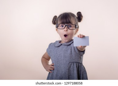 Cute smiling child with glasses holding discount white card in her hands. Kid with credit card. Little girl showing empty blank paper note, copy space. Isolated on pink background