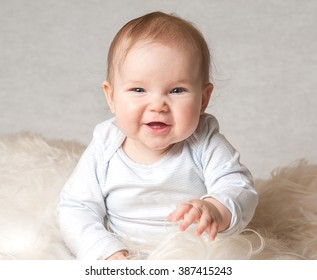 Cute smiling child on a white bed. First teeth. health 6 months baby girl sitting. textile for infant nursery