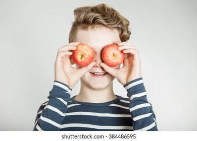 Cute smiling child in striped blue and white shirt holding apples in front of his eyes over gray background