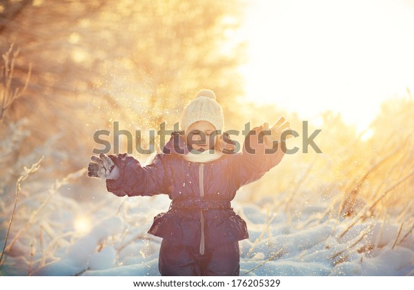 A cute smiling child in the warm clothing playing with snow on a frosty winter day