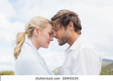 Cute smiling couple standing outside facing each other on a chilly day
