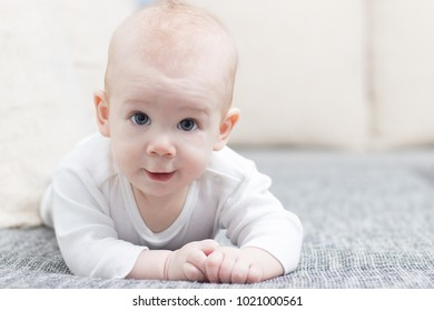 Cute, smiling, crawling baby boy on grey couch, wearing white dress.