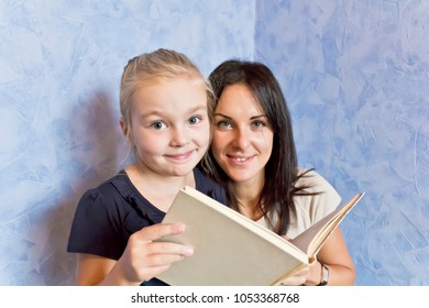 Cute smiling daughter are reading a book with her mother