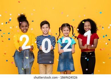 Cute lächelnde verschiedene Kinder mit Zahlen 2021 feiern neues Jahr einzeln auf gelbem Hintergrund
