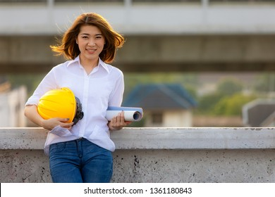 Cute smiling face of Asian female engineer holding blueprint and yellow safty helmet looking to camera with self confident manner on rooftop of construction site.