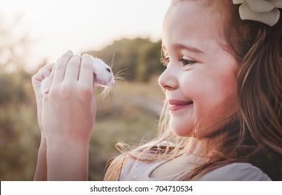 Cute smiling girl holding white hamster - Retro look