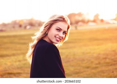 Cute smiling girl looking at you on a sunny day