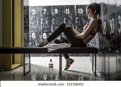Cute smiling girl with a mobile phone sits sideways on the bench in the locker-room in the gym. She wears multi-colored sneakers, black pants and a pink top. Horizontal.