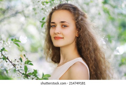 Cute smiling girl outdoors, sunny spring portrait young girl, curly hair