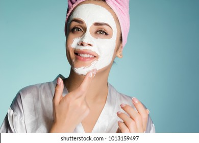 cute smiling girl with pink towel on head applying white moisturizing mask on face