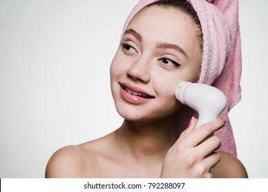cute smiling girl with a pink towel on her head doing a deeper cleansing of the skin of her face with an electric brush