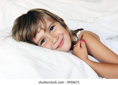 A cute smiling girl relaxing in a bed