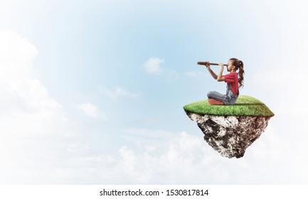 Lächelndes Mädchen, das auf einer schwimmenden Insel hoch oben am Himmel sitzt