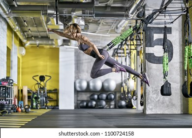 Cute smiling girl is training with goflo-trainer in the gym. She is jumping in the air with outstretched right arm. Woman wears a gray top and pants, violet sneakers. Horizontal.