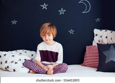 cute smiling kid in pajamas sitting on bed in nursery room