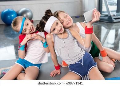Cute smiling kids taking selfie with smartphone in gym, children sport school concept