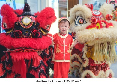 Cute smiling little 2 - 3 years old Asian toddler baby boy child in traditional red Chinese costume celebrating Chinese New Year with Chinese lion dance in Bangkok, Lunar New Year celebration concept