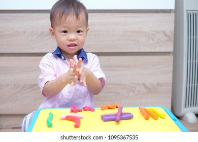 Cute smiling little Asian 18 months old toddler baby boy child having fun playing modeling clay / play dought at play school / child care, Montessori education Creative play for toddlers concept
