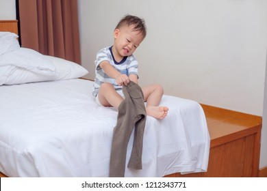 Cute smiling little Asian 2 years old toddler boy child sitting in bed concentrate on putting on his pants, Encourage Self-Help Skills in Children, The growth of independence in young child concept