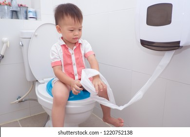 Cute smiling little Asian 2 year old toddler baby boy child sitting on toilet modern style with a kid bathroom accessory and holding & playing with toilet paper. Potty / Toilet Training child concept