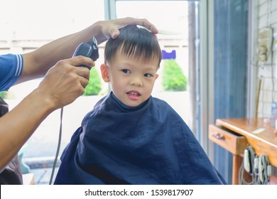 Cute smiling little Asian 3 - 4 years old toddler baby boy child getting a haircut at the hairdresser's barber shop, Kid cut with hairdresser's machine