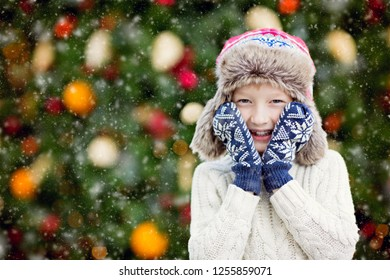 cute smiling little boy at christmas time with decorated tree in the background, magical christmas time concept, copy space on left, snowing
