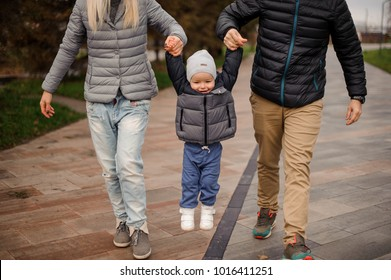 Cute smiling little boy holding parents hands and jumping walking down the street on a cloudy day
