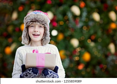 cute smiling little boy holding christmas presents with decorated tree in the background, magical christmas time concept, copy space on right