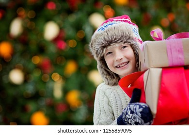 cute smiling little boy holding christmas presents with decorated tree in the background, magical christmas time concept, copy space on left