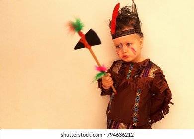 Cute smiling little boy in an Indian costume posing against the wall, a hatchet in his hand, hair is disheveled. Ready for Purim party