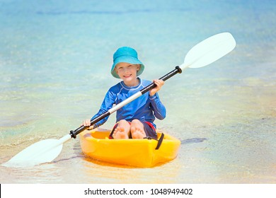 cute smiling little boy in the kayak holding paddle enjoying active vacation at the tropical island at fiji, south pacific